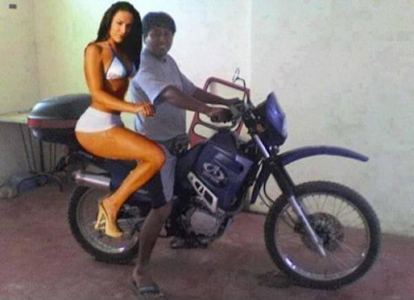 Chico con moto y una modelo detras